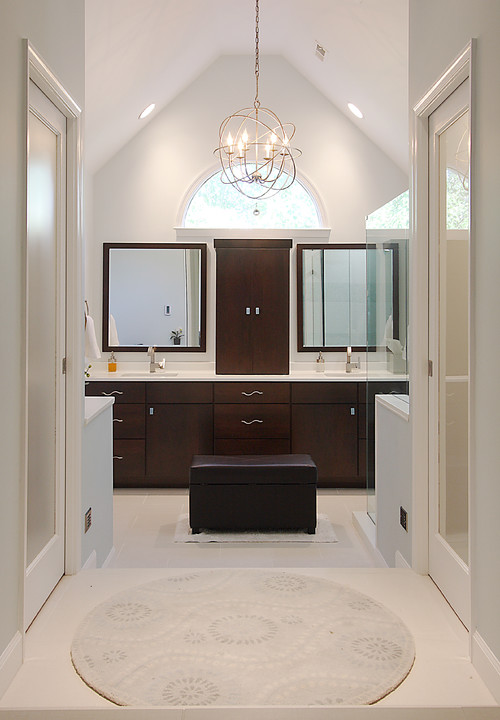 A master bathroom remodel with high, vaulted ceilings, his and her vanities and contemporary style.
