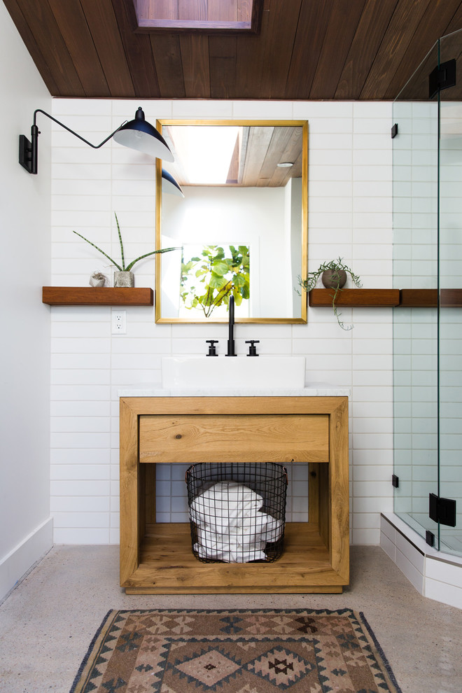 Small trendy 3/4 white tile concrete floor and gray floor corner shower photo in Salt Lake City with open cabinets, medium tone wood cabinets, white walls, a vessel sink, a hinged shower door and white countertops