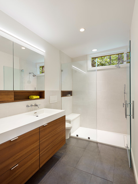 Walk-in shower - small modern master yellow tile and porcelain tile porcelain floor and gray floor walk-in shower idea in Baltimore with flat-panel cabinets, brown cabinets, a wall-mount toilet, white walls, an integrated sink, solid surface countertops and a hinged shower door