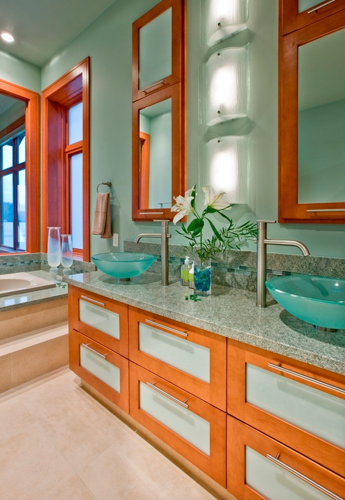 Inspiration for a contemporary master green tile drop-in bathtub remodel in Seattle with a vessel sink, glass-front cabinets, medium tone wood cabinets, granite countertops, green walls and green countertops