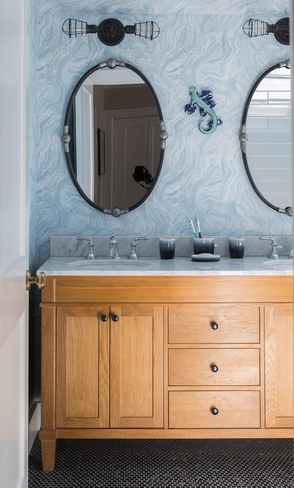 Beach style mosaic tile floor and black floor bathroom photo in New York with furniture-like cabinets, medium tone wood cabinets, blue walls, an undermount sink and white countertops