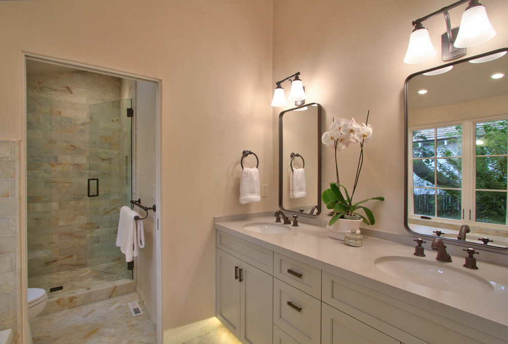 Mid-sized transitional master beige tile and marble tile porcelain tile and beige floor bathroom photo in Other with shaker cabinets, white cabinets, beige walls, an undermount sink, solid surface countertops and a hinged shower door