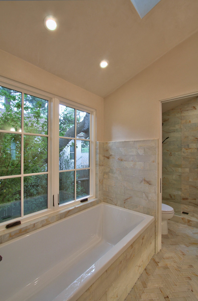 Inspiration for a mid-sized transitional master beige tile and marble tile porcelain tile and beige floor bathroom remodel in Other with shaker cabinets, white cabinets, beige walls, an undermount sink, solid surface countertops and a hinged shower door
