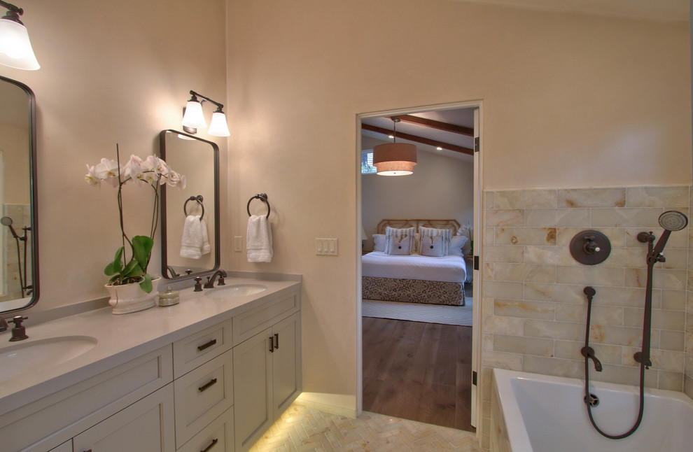 Example of a mid-sized transitional master beige tile and marble tile porcelain tile and beige floor bathroom design in Other with shaker cabinets, white cabinets, beige walls, an undermount sink, solid surface countertops and a hinged shower door
