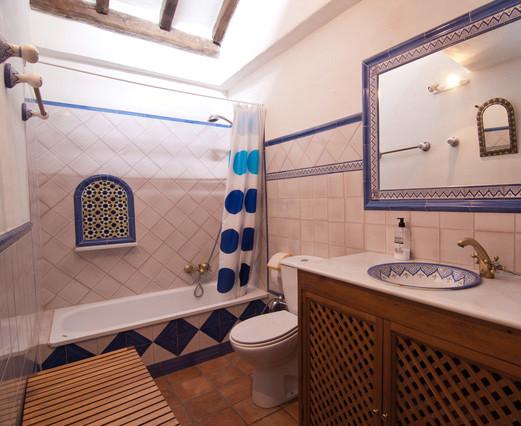 Diseño de cuarto de baño principal, marinero, de tamaño medio, con suelo de baldosas de terracota, bañera empotrada, combinación de ducha y bañera, sanitario de dos piezas, paredes blancas y lavabo bajoencimera