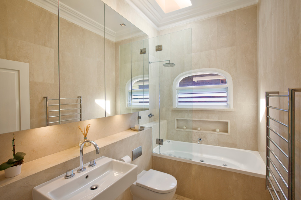 Inspiration for a transitional bathroom in Sydney with a wall-mount sink, flat-panel cabinets, an alcove tub, a shower/bathtub combo, a wall-mount toilet, beige tile, stone tile and beige walls.