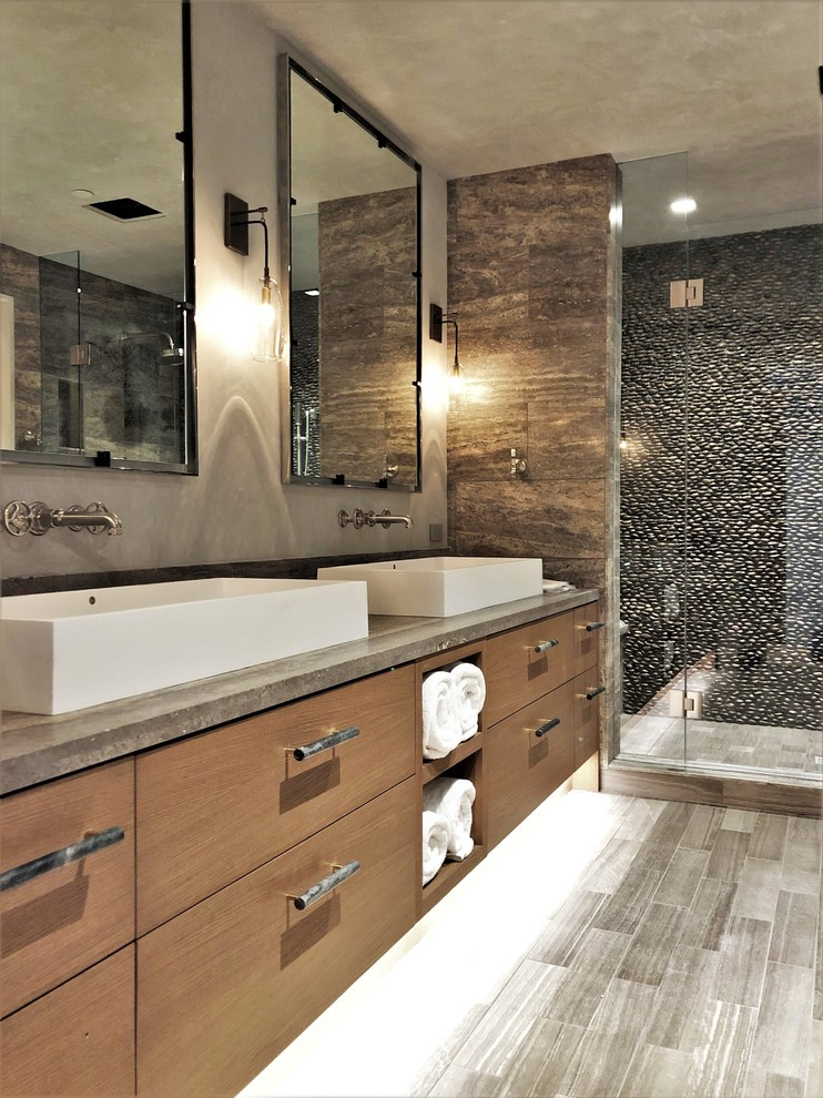 Inspiration for a large contemporary master stone tile porcelain tile and gray floor alcove shower remodel in Denver with flat-panel cabinets, medium tone wood cabinets, a two-piece toilet, multicolored walls, a vessel sink, concrete countertops, a hinged shower door and gray countertops