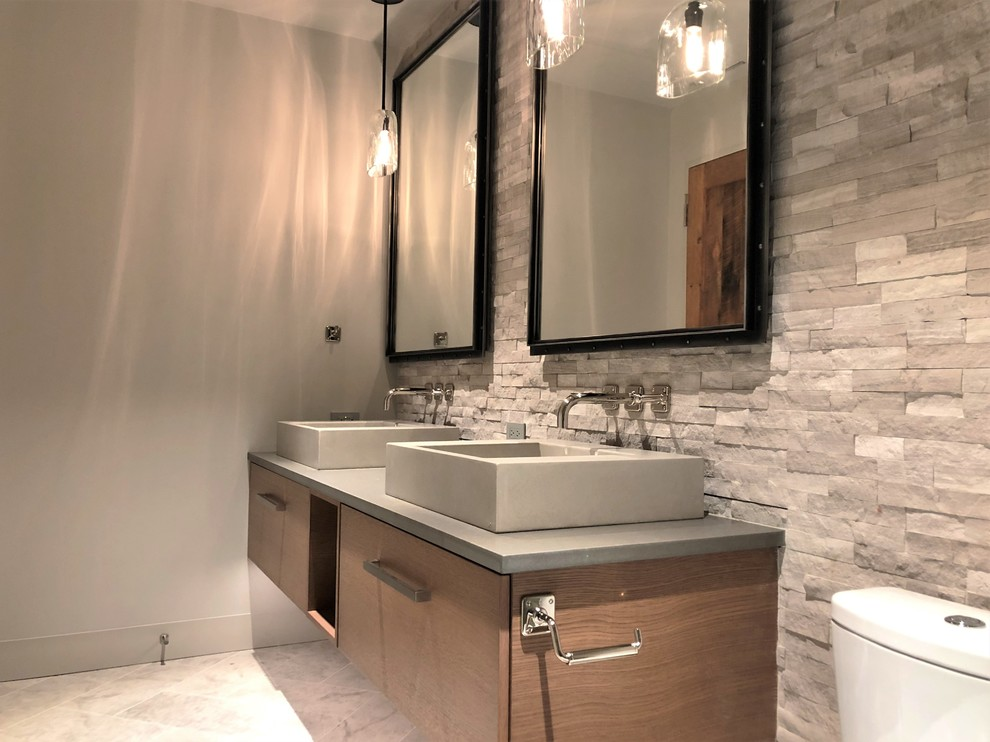 Mid-sized trendy gray tile and stone tile marble floor and gray floor alcove shower photo in Denver with flat-panel cabinets, medium tone wood cabinets, a two-piece toilet, gray walls, a vessel sink, quartzite countertops and gray countertops