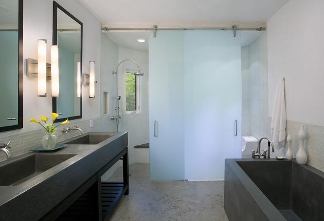 concrete floor bathroom idea in san francisco with concrete countertops and open cabinets