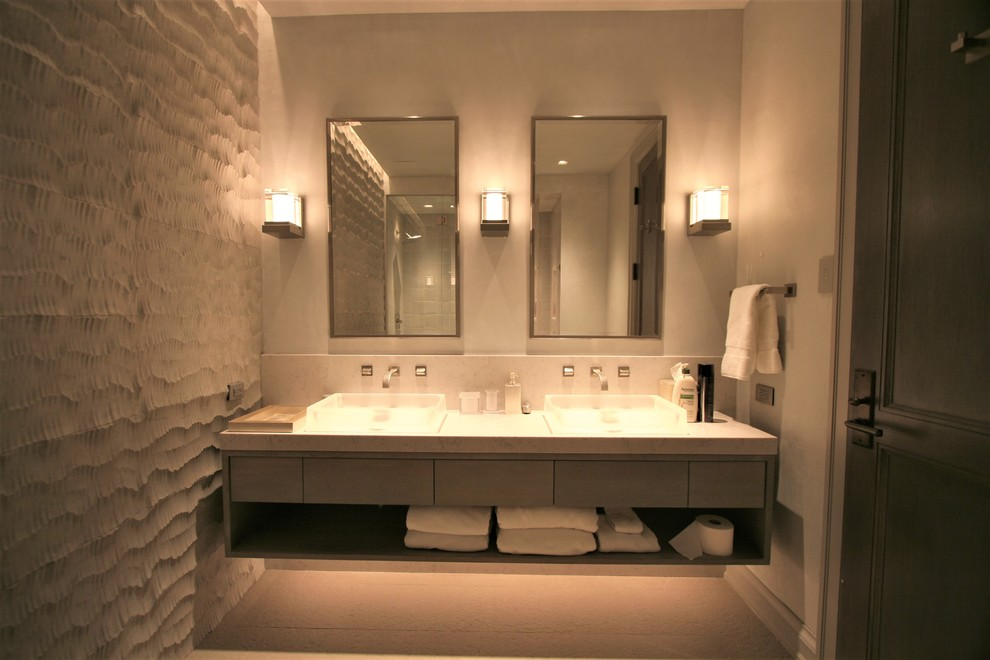 Example of a mid-sized minimalist 3/4 bathroom design in Denver with flat-panel cabinets, a vessel sink, gray cabinets, gray walls and solid surface countertops