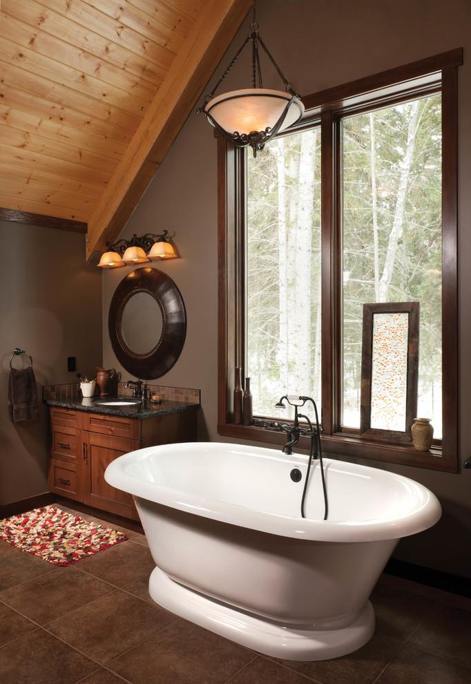 Imagen de cuarto de baño principal, rústico, de tamaño medio, con lavabo bajoencimera, armarios estilo shaker, puertas de armario de madera oscura, encimera de granito, bañera exenta, baldosas y/o azulejos marrones y paredes grises