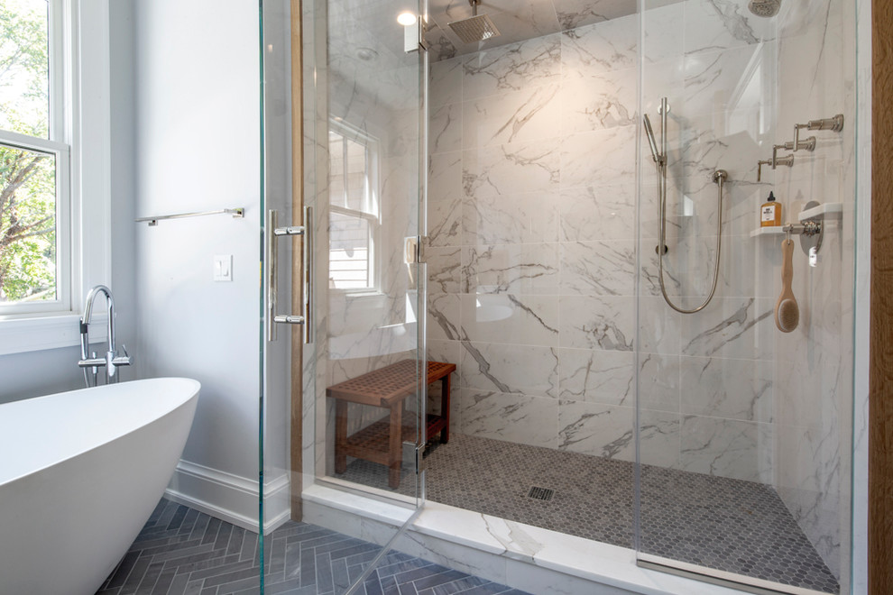 Example of a large minimalist master marble floor and gray floor freestanding bathtub design in New York with medium tone wood cabinets, a one-piece toilet, gray walls, marble countertops, a hinged shower door and white countertops