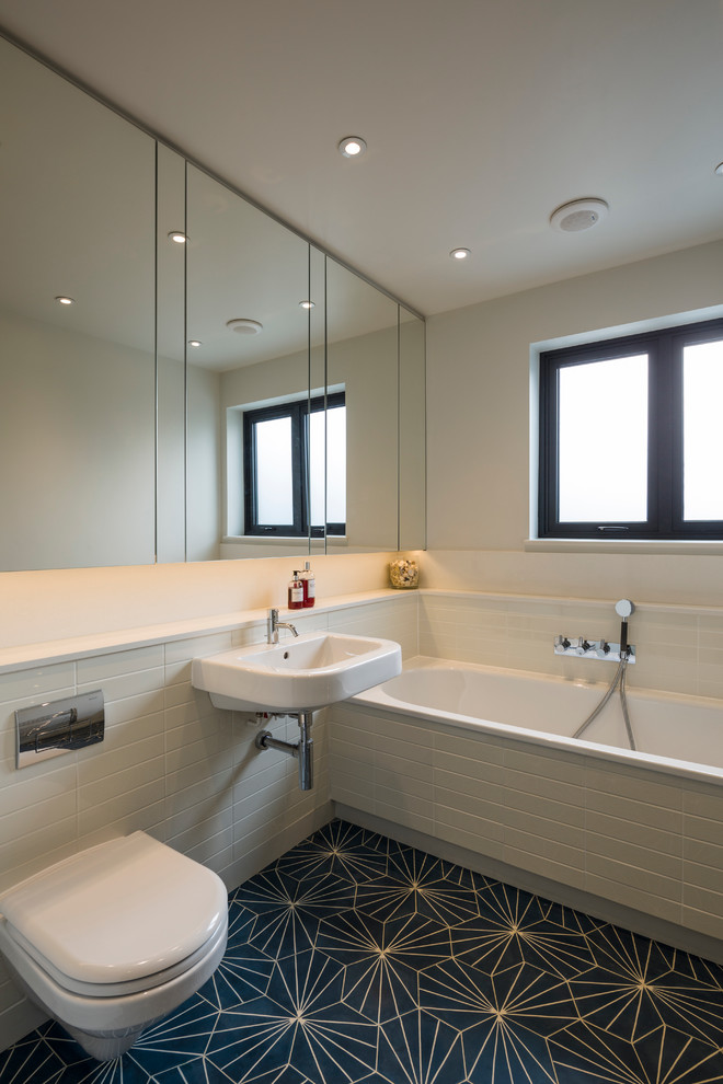 Example of a danish white tile bathroom design in London with quartz countertops, a wall-mount toilet, a wall-mount sink and white walls