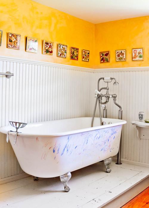 banheiro tem metade da parede em madeira branca e a outra metade da parede amarela, com banheira antiga e manchada