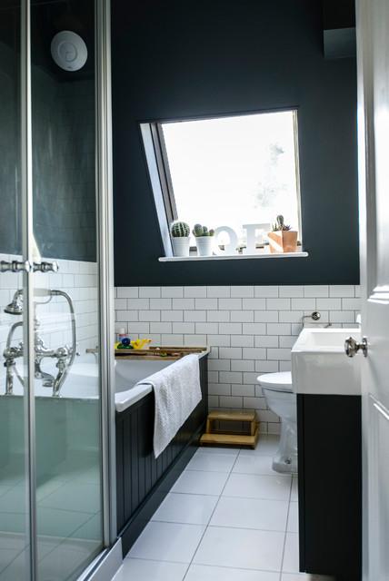 Inspiration för ett vintage badrum, med ett integrerad handfat, svarta skåp, ett platsbyggt badkar och svarta väggar