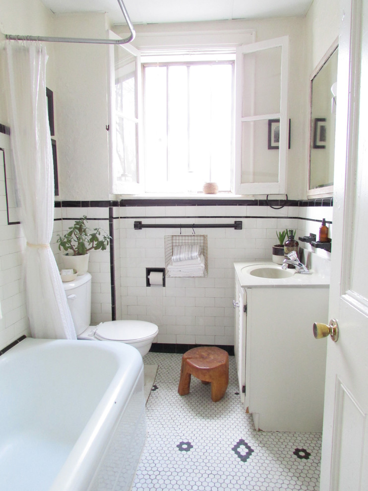 Elegant subway tile and black and white tile white floor bathroom photo in Toronto with white cabinets, a two-piece toilet and white countertops