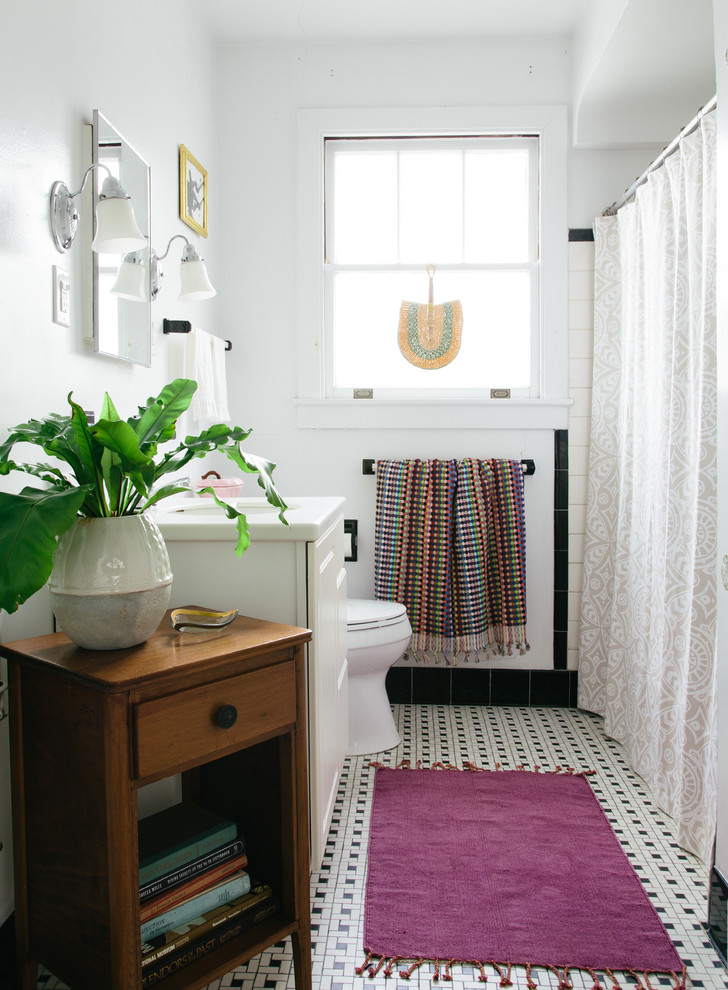 Inspiration for a mid-sized eclectic 3/4 black tile, black and white tile, white tile and porcelain tile porcelain floor and multicolored floor tub/shower combo remodel in New Orleans with furniture-like cabinets, white cabinets, white walls, an undermount sink, solid surface countertops and white countertops