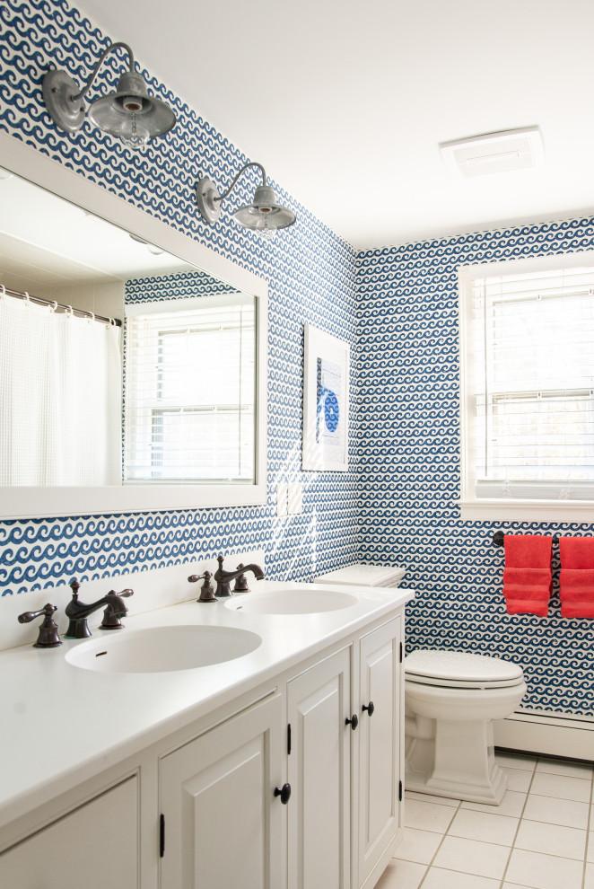 Ejemplo de cuarto de baño infantil, marinero, con armarios con paneles con relieve, puertas de armario blancas, sanitario de dos piezas, paredes multicolor, suelo blanco, ducha con cortina y encimeras blancas