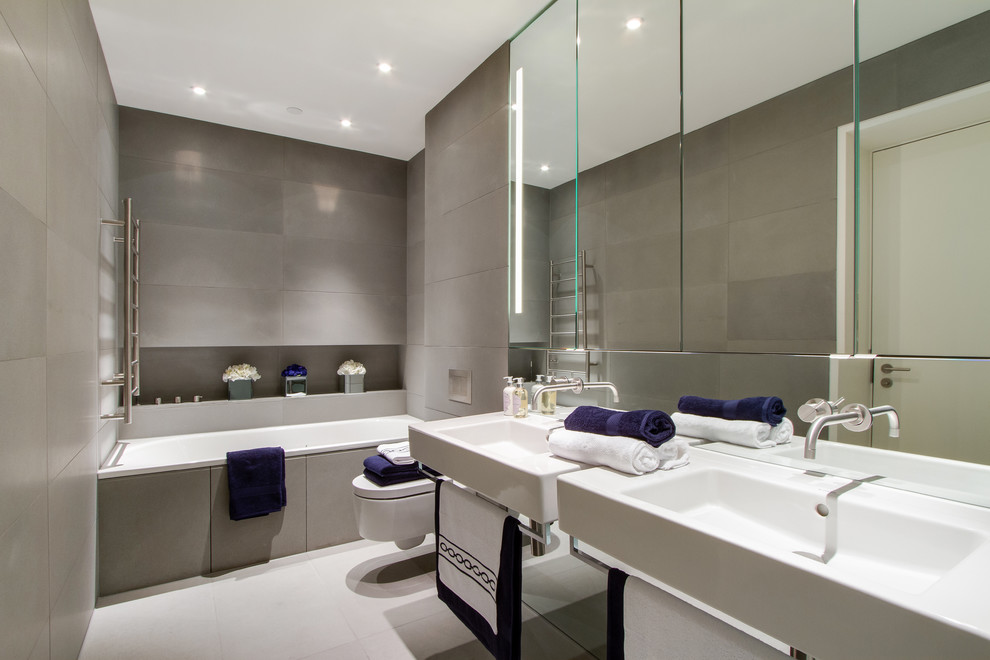 Drop-in bathtub - contemporary gray tile drop-in bathtub idea in London with a wall-mount sink and a wall-mount toilet