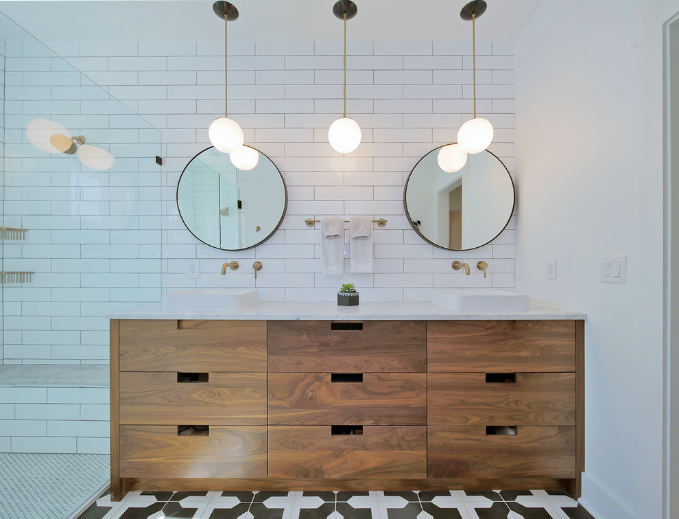 Inspiration for a coastal white tile multicolored floor corner shower remodel in Jacksonville with flat-panel cabinets, medium tone wood cabinets, white walls, a vessel sink and white countertops