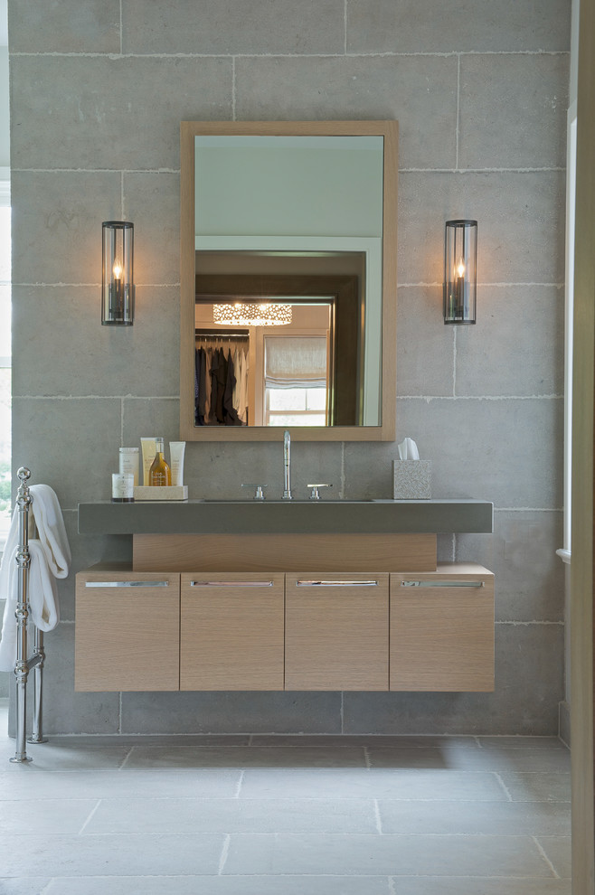 Inspiration for a mid-sized transitional gray tile concrete floor bathroom remodel in New York with flat-panel cabinets, light wood cabinets, gray walls, an undermount sink and solid surface countertops