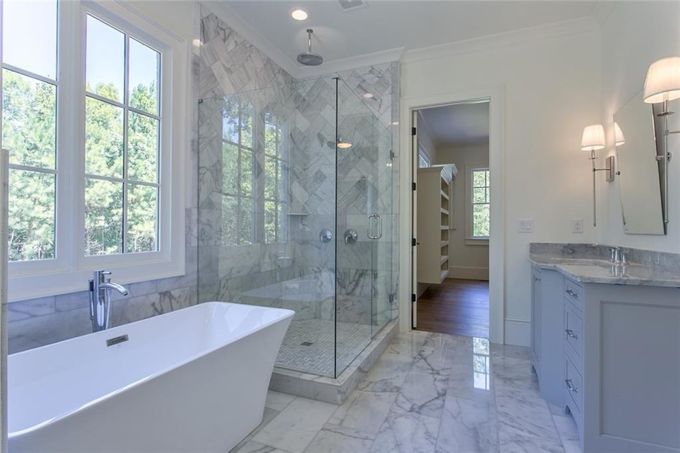 Example of a large transitional master gray tile and marble tile marble floor and gray floor bathroom design in Atlanta with recessed-panel cabinets, gray cabinets, a two-piece toilet, white walls, an undermount sink, marble countertops, a hinged shower door and gray countertops