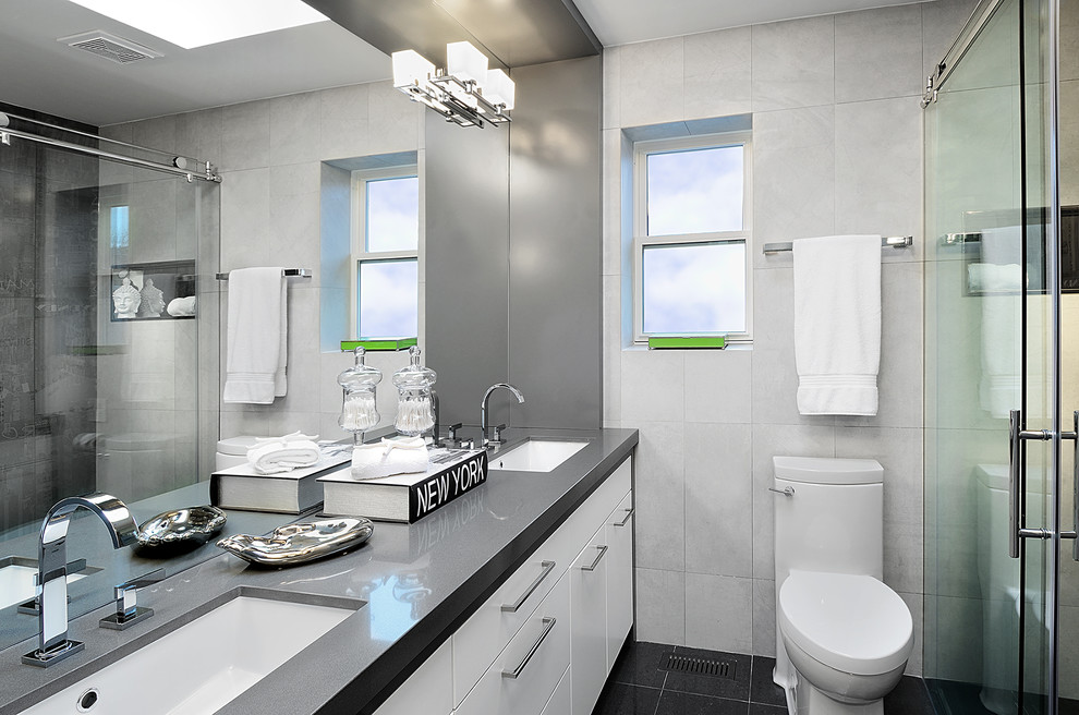 Bathroom - contemporary white tile bathroom idea in Toronto with an undermount sink, flat-panel cabinets, white cabinets and gray countertops