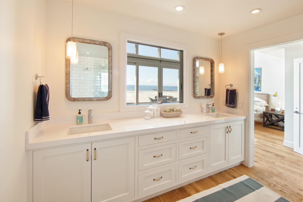 Example of a mid-sized beach style master white tile and subway tile light wood floor alcove shower design in Orange County with an undermount sink, beaded inset cabinets, white cabinets, white walls, solid surface countertops and white countertops