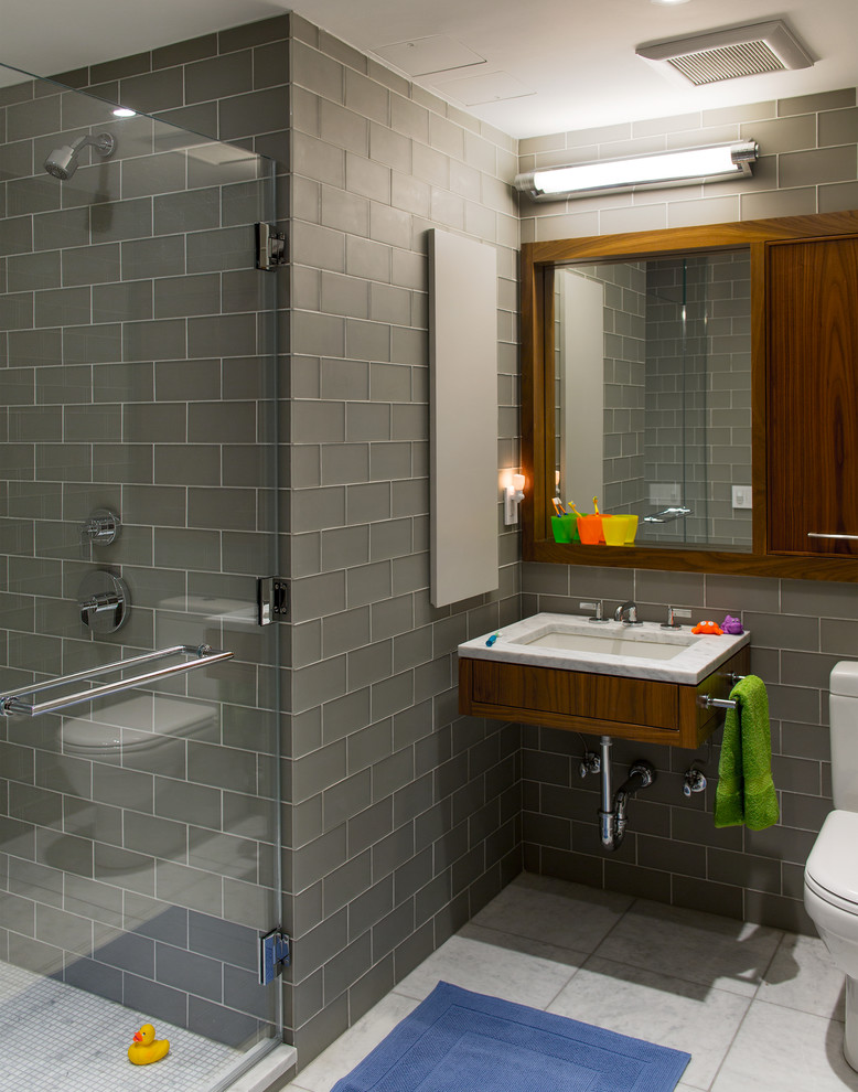 Example of a trendy gray tile and subway tile alcove shower design in New York with a wall-mount sink and medium tone wood cabinets