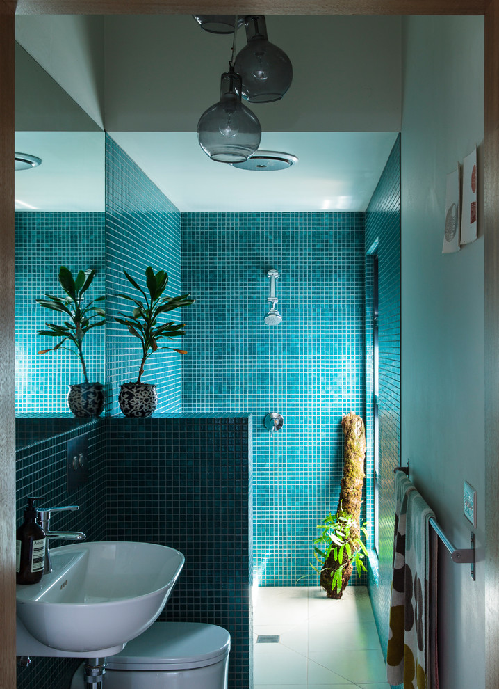 Example of a small trendy master green tile and mosaic tile ceramic tile doorless shower design in Melbourne with open cabinets, white cabinets, a wall-mount toilet, white walls, a wall-mount sink and tile countertops