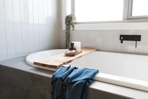 built in bath with timber bath caddy