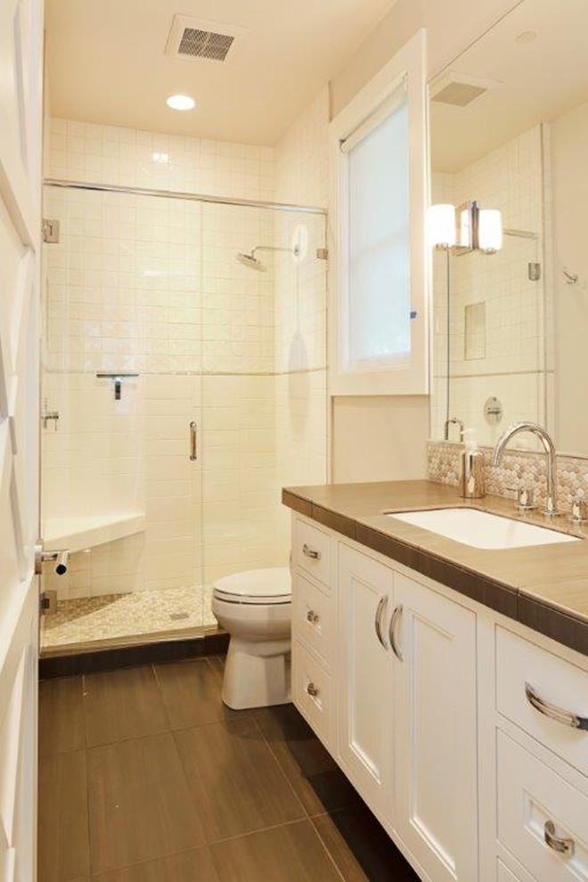 Example of a trendy porcelain tile bathroom design in Portland with an undermount sink, recessed-panel cabinets, white cabinets and tile countertops
