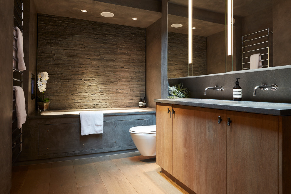 Example of a mid-sized trendy gray tile light wood floor and beige floor bathroom design in London with flat-panel cabinets, light wood cabinets, a wall-mount toilet, gray walls, gray countertops, an undermount tub, an integrated sink and concrete countertops