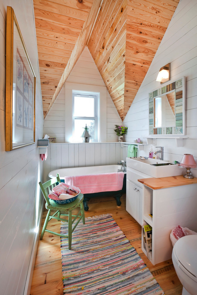 Inspiration for a country medium tone wood floor claw-foot bathtub remodel in Minneapolis with a console sink, white cabinets and white walls