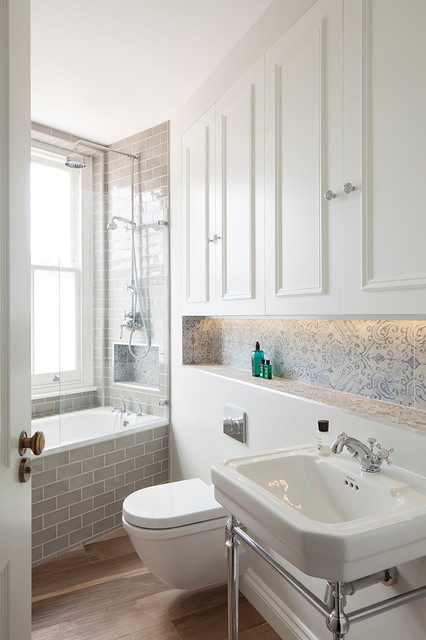 Design ideas for a victorian bathroom in London with a console sink, white cabinets, a built-in bath, a shower/bath combination, porcelain tiles, medium hardwood flooring, a wall mounted toilet and recessed-panel cabinets.