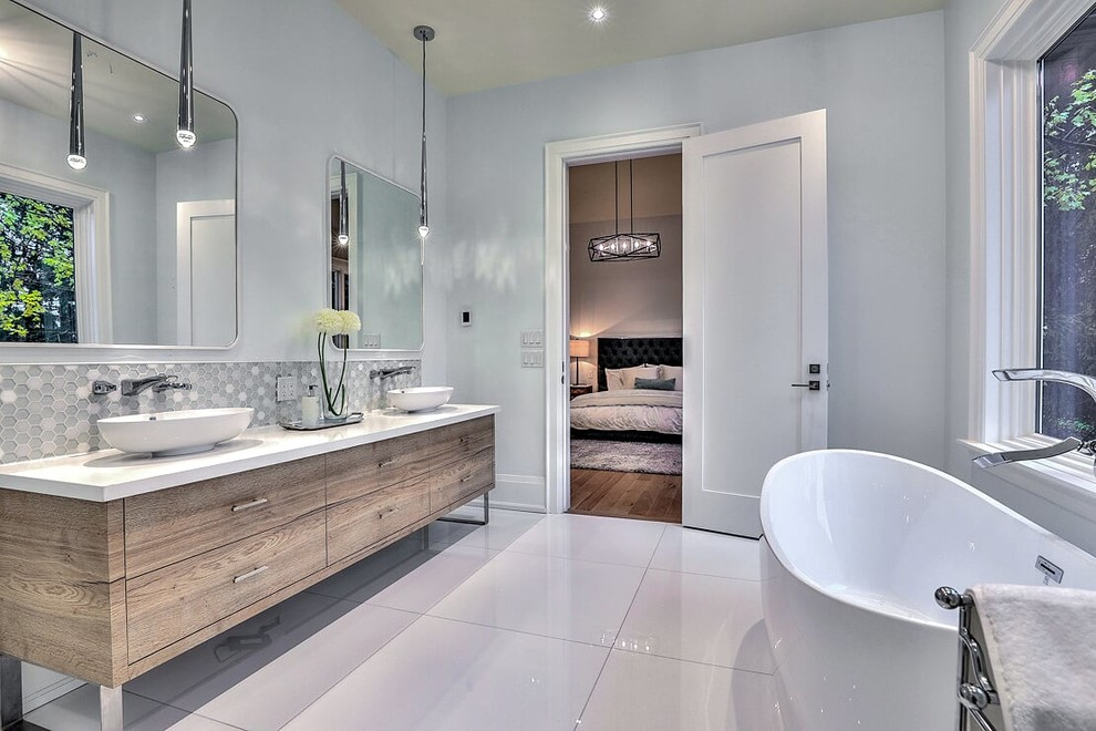 Large trendy master gray tile and ceramic tile ceramic tile and white floor freestanding bathtub photo in Toronto with flat-panel cabinets, medium tone wood cabinets, a two-piece toilet, white walls, a vessel sink, solid surface countertops and white countertops