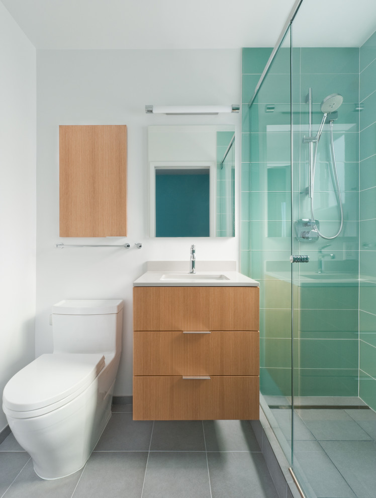 Example of a trendy blue tile and glass tile alcove shower design in San Francisco with an undermount sink, flat-panel cabinets, a one-piece toilet and light wood cabinets