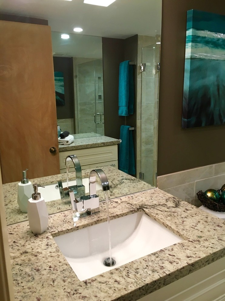Large island style 3/4 gray tile and porcelain tile pebble tile floor and beige floor alcove shower photo in Other with raised-panel cabinets, white cabinets, a two-piece toilet, gray walls, an undermount sink, a hinged shower door, granite countertops and gray countertops