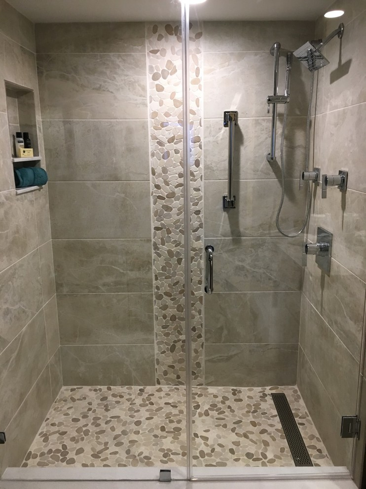 Large island style 3/4 gray tile and porcelain tile pebble tile floor and beige floor bathroom photo in Other with gray walls, a hinged shower door, raised-panel cabinets, an undermount sink, granite countertops, white cabinets, a two-piece toilet and gray countertops