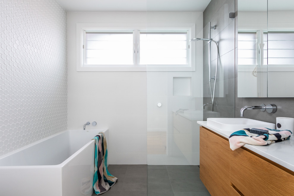 Inspiration for a contemporary wet room bathroom in Sydney with white tile, gray tile, ceramic tile, white walls, ceramic floors, a drop-in sink, engineered quartz benchtops, grey floor, an open shower, white benchtops, flat-panel cabinets, medium wood cabinets and a corner tub.