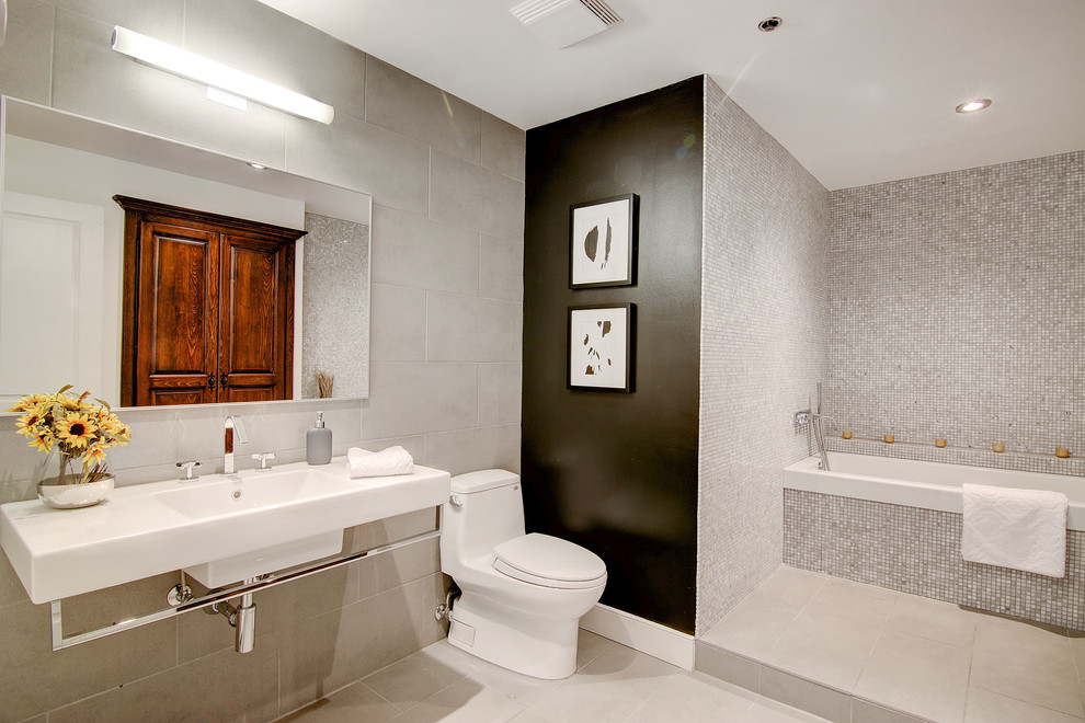 Inspiration for a mid-sized contemporary master gray tile and mosaic tile porcelain floor and beige floor bathroom remodel in Montreal with a one-piece toilet, gray walls, a wall-mount sink and solid surface countertops