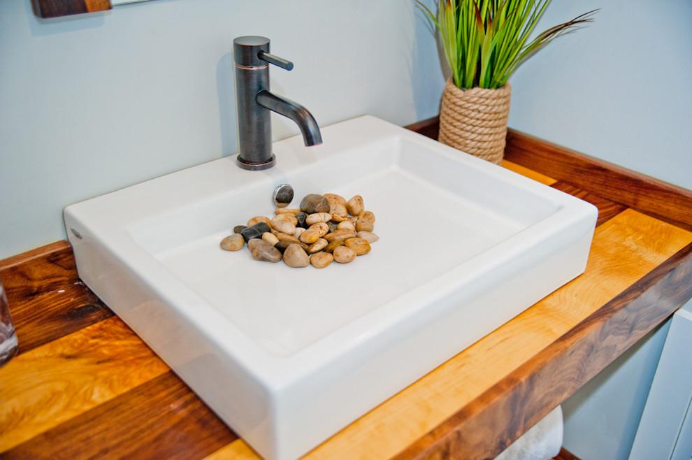 Diseño de cuarto de baño actual, pequeño, con lavabo sobreencimera, encimera de madera, sanitario de una pieza, paredes grises, suelo de madera en tonos medios y aseo y ducha