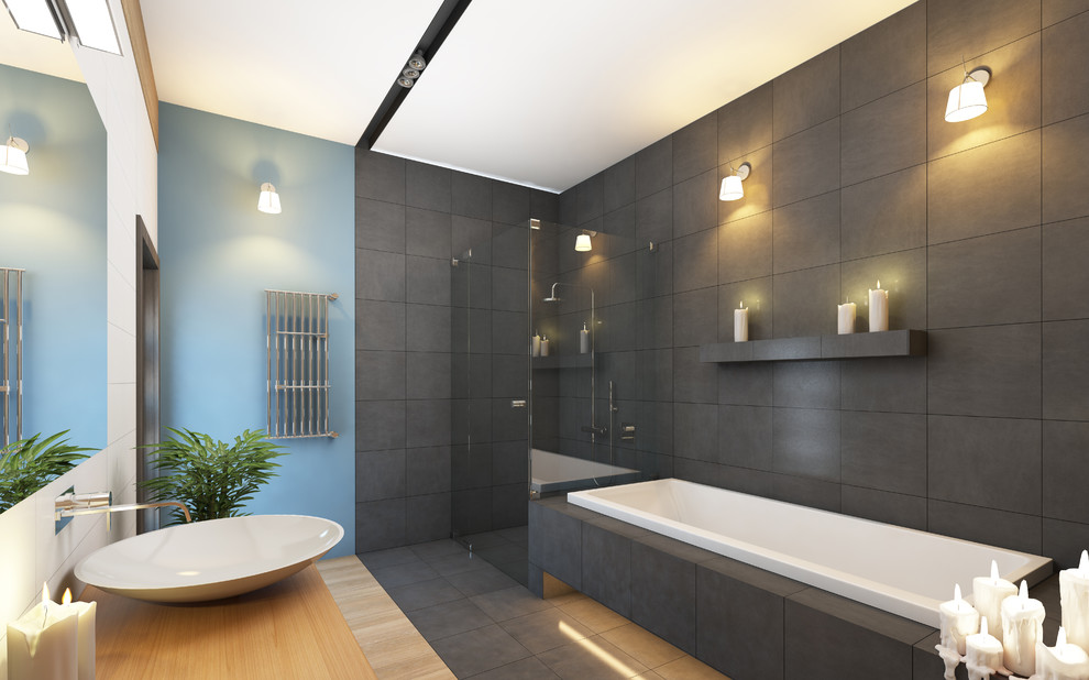 Large minimalist master gray tile and porcelain tile bamboo floor and gray floor bathroom photo in Toronto with flat-panel cabinets, light wood cabinets, a two-piece toilet, blue walls, a vessel sink, wood countertops and a hinged shower door