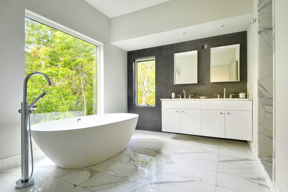 Large trendy master white tile and stone tile marble floor and gray floor bathroom photo in Boston with marble countertops, flat-panel cabinets, white cabinets, white walls and an undermount sink