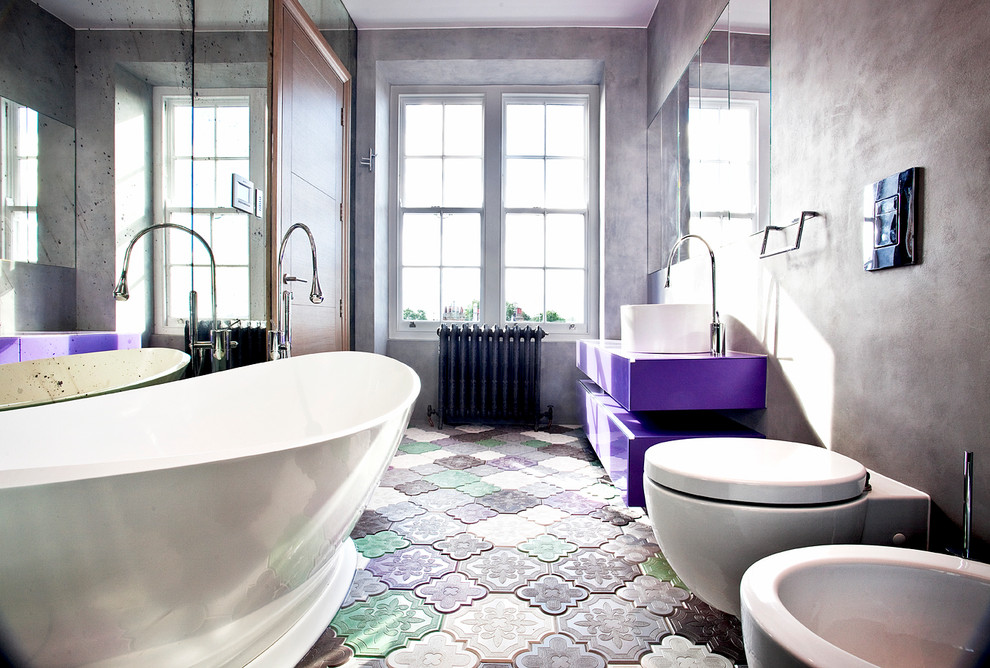 Design ideas for a contemporary bathroom in London with a vessel sink, flat-panel cabinets, a freestanding tub, a wall-mount toilet, grey walls and multi-coloured floor.