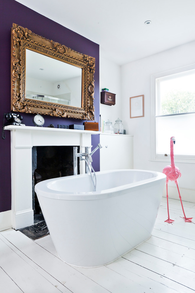 Inspiration for an eclectic painted wood floor freestanding bathtub remodel in London with purple walls