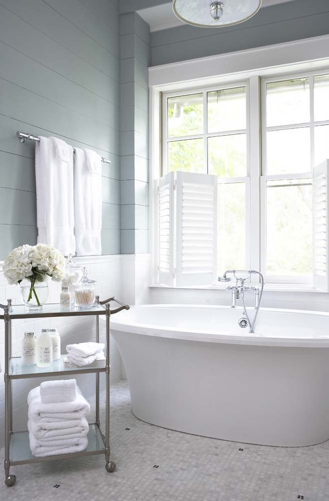 Example of a large classic master subway tile and white tile mosaic tile floor freestanding bathtub design in Charleston with blue walls