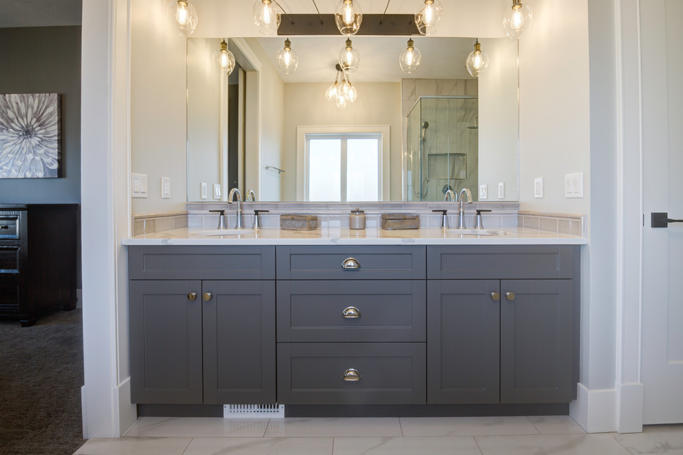 Large elegant master marble tile marble floor and white floor corner bathtub photo in Other with recessed-panel cabinets, blue cabinets, a two-piece toilet, gray walls, an undermount sink, quartzite countertops and white countertops