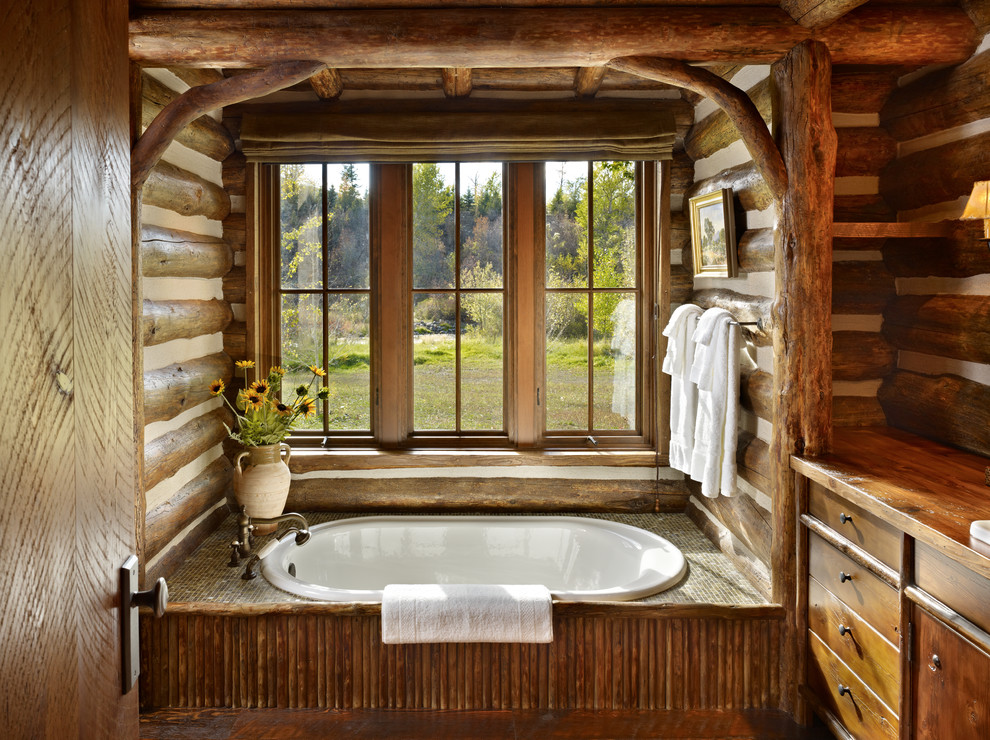 Drop-in bathtub - large rustic master drop-in bathtub idea in Other with dark wood cabinets, brown walls, wood countertops, furniture-like cabinets and brown countertops