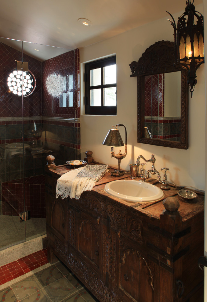 Inspiration for a mediterranean alcove shower remodel in Phoenix with a drop-in sink, furniture-like cabinets and dark wood cabinets